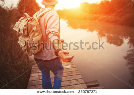 stock-photo-traveler-with-backpack-walking-over-wooden-bridge-on-the-lake-in-sunset-250767271